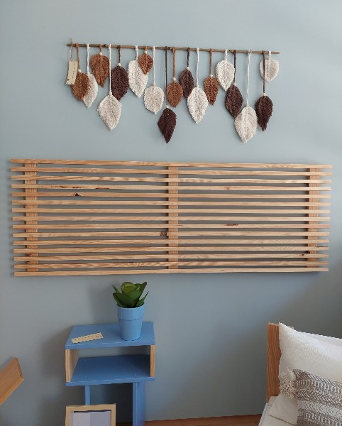 Cabecero en madera maciza adornado con tapiz otoñal.